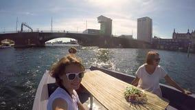 Drie jonge gelukkige meisjes zijn roeien door een kanaal in Kopenhagen stock video
