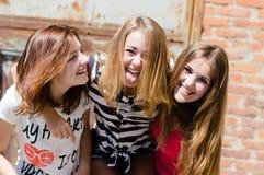 Drie jonge gelukkige tieners hebben pret in openlucht in stad royalty-vrije stock foto's