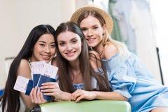Drie jonge glimlachende vrouwen die paspoorten en kaartjes houden terwijl het verpakking van koffer die klaar aan worden royalty-vrije stock foto