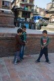 Drie jonge jongens die een spel met een muntstuk in de straat, Katmandu, Nepal, Maart 2014 spelen royalty-vrije stock afbeelding