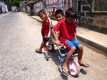 Drie jonge jongens die met een geïmproviseerde rit spelen stock foto