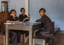 Drie jonge jongensmonniken die in klaslokaal bij Koninklijk Boeddhistisch T bestuderen Stock Afbeeldingen