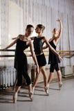Drie jonge leuke ballerina's voeren oefeningen op een choregrafische machine of een staaf uit stock afbeelding