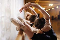 Drie jonge leuke ballerina's voeren oefeningen op een choregrafische machine of een staaf uit royalty-vrije stock afbeelding