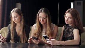 Drie jonge meisjes die in een koffie met in hand telefoons zitten, de telefoonverslaving