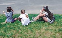 Drie jonge meisjes die in gras, achtermening zitten stock fotografie