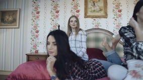 Drie jonge meisjes die ontspannen op bed in modieus huis hebben 4K stock videobeelden
