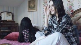 Drie jonge meisjes die ontspannen op bed in modieus huis hebben 4K stock footage