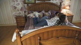 Drie jonge meisjes die ontspannen op bed in modieus huis hebben langzaam stock video