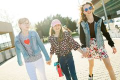 Drie jonge meisjes die op stadsstraten lopen royalty-vrije stock afbeelding