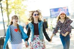 Drie jonge meisjes die op stadsstraten lopen stock afbeelding