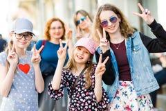Drie jonge meisjes die op stadsstraten stellen - overwinning - pret in stock foto