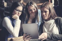 Drie jonge meisjes die samen thuis op iets letten o stock foto's