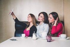 Drie jonge meisjes die selfie in een koffie nemen Royalty-vrije Stock Foto's
