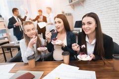 Drie jonge meisjes die zoete cake eten bij lunchtijd in bureau Portret van jonge vrouw op wit stock afbeelding
