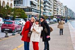 Drie jonge meisjes maken met mono-peul op de Straat van Leof Nikis in Thessaloniki Griekenland Maart 2018 selfy De toeristen make royalty-vrije stock fotografie