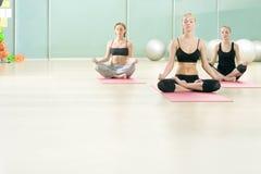 Drie jonge meisjes mediteren in sportengymnastiek Royalty-vrije Stock Foto's