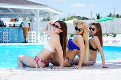 Drie jonge meisjes op de achtergrond van de pool stock foto's