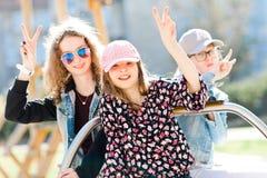 Drie jonge meisjes op speelplaatszitting op kleine carrousel - vict stock foto's