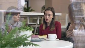 Drie jonge meisjes zitten in koffie, vrienden, bedrijf, roddels, dialoog, bespreking Meisjes in het koffieconcept stock footage