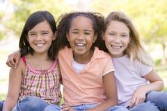 Drie jonge meisjesvrienden die in openlucht zitten Royalty-vrije Stock Foto's