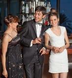 Drie jonge mensen bij en staaf die drinkt flirt royalty-vrije stock foto's