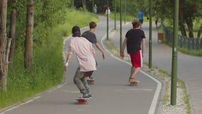 Drie jonge mensen die in het groene park op de vlotte weg met een skateboard rijden stock footage