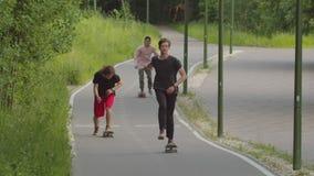 Drie jonge mensen die in het park op de vlotte weg met een skateboard rijden stock video