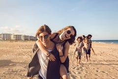 Drie jonge mensen die hun meisjes geven vervoeren per kangoeroewagen ritten Royalty-vrije Stock Foto