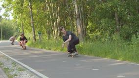 Drie jonge mensen die op de weg in het groene die park met een skateboard rijden door bos wordt omringd stock footage