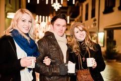 Drie jonge Mensen die Stempel drinken Stock Fotografie