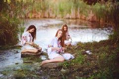 Drie jonge mooie meisjes die in witte overhemden met bloemenornamenten met kronen in hun handen op de achtergrond zitten royalty-vrije stock foto's