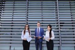 Drie jonge ondernemers moderne, opgeleide studenten, kerel en twee stock afbeelding