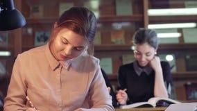 Drie jonge studenten die in bibliotheek zitten en hun zaken doen stock video