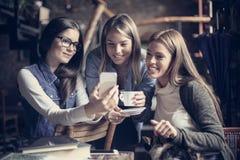Drie jonge studenten die in koffie genieten van royalty-vrije stock foto's