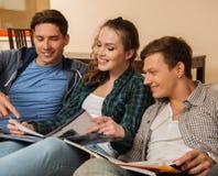 Drie jonge studenten die voor examens voorbereidingen treffen Stock Foto's
