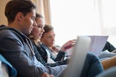 Drie jonge studenten die voor examens voorbereidingen treffen Stock Foto