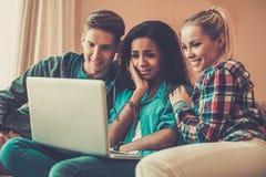 Drie jonge studenten in huisbinnenland Stock Afbeelding