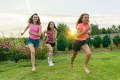 Drie jonge tieners die van sportenmeisjes op een groen gazon tegen de achtergrond van de zomerzonsondergang lopen stock afbeeldingen
