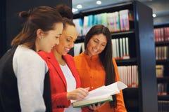 Drie jonge universitaire studenten die samen bestuderen Stock Foto