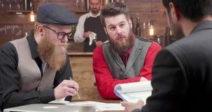 Drie jonge verkopers die een commerciële vergadering in een lokale koffiewinkel hebben stock video