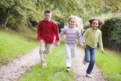 Drie jonge vrienden die op een weg in openlucht lopen royalty-vrije stock afbeelding