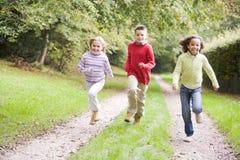 Drie jonge vrienden die op een weg in openlucht lopen royalty-vrije stock fotografie