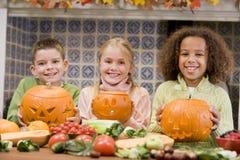 Drie jonge vrienden op Halloween met pompoenen Royalty-vrije Stock Foto