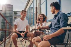 Drie jonge vrienden samen bij openluchtkoffie royalty-vrije stock afbeelding