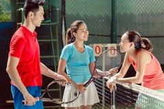 Drie jonge vrolijke spelers die alvorens dubbelen samen te spelen aanpas spreken royalty-vrije stock foto's