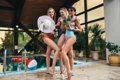 Drie jonge vrouwelijke modellen die in zwempakken stellen die ananassen, hoed en sap houden bij zwembad op kuuroordcentrum Stock Foto