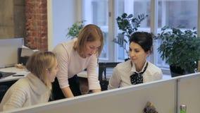 Drie jonge vrouwelijke ontwerpers bespreken het project in het moderne bureau stock video
