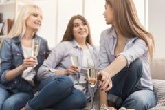 Drie jonge vrouwelijke vrienden die champagne drinken stock foto's