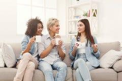Drie jonge vrouwelijke vrienden die met koffie thuis babbelen Royalty-vrije Stock Fotografie